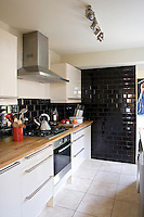 In contrast to the retro feel of the rest of the house the kitchen has been designed in a contemporary style with a wall lined in dramatic black subway tiles