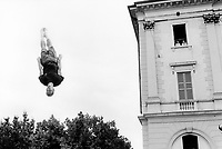 Switzerland. Canton Ticino. Lugano. A young man does trampoline and flies in the air in front of the Town Hall building. A man and a woman, both working for the police force, look at the show from a window. © 1992 Didier Ruef