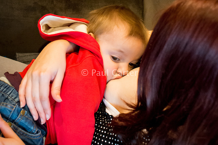 A woman breastfeeds her one year old toddler in a coffee shop.<br /> <br /> Image from the &quot;We Do It In Public&quot; documentary photography project collection: <br />  www.breastfeedinginpublic.co.uk<br /> <br /> Dorset, England, UK<br /> 17/04/2013