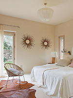 A pair of sunburst mirrors on the bedroom wall which has a calming neutral colour scheme