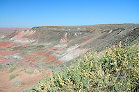 Navajo County, Arizona – A view of the Painted Desert shows a hill with black basalt at the top contrasting with the colorful Chinle formation below. The Painted Desert is a broad region of rocky badlands featuring unique rocks in a variety of hues - lavenders, grays, reds, oranges and pinks. Located in Northeastern Arizona, the Painted Desert attracts hundreds of thousands a visitors each year. Photo by Eduardo Barraza © 2014