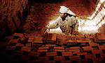 A woman in Luang Prabang, Laos, stacking bricks in a kiln.