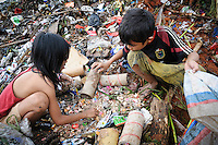 Ashuar, 12, and Sida, 8, searching for packets of stickers amongst discarded waste on the 'Trash mountain', Makassar, Sulawesi, Indonesia.
