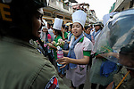 A woman protester offers water to a sweating police officer as informal sector workers, including domestic workers and tuk-tuk drivers, attempt to protest in Phnom Penh on December 10, 2012. Observing International Human Rights Day, they were calling for the Cambodian government to ratify ILO Convention 189 guaranteeing the rights of domestic workers, and planned to take their request to the prime minister's office, but police stopped them far short of their goal.