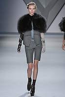 Anabela Belikova walks runway in a grey mélange wool sleeveless jacket with oversized charcoal raccoon cropped cape over column print long sleeve draped blouse, with grey mélange wool bermuda short, from the Vera Wang Fall 2012 Vis-a-gris collection, during Mercedes-Benz Fashion Week Fall 2012 in New York.