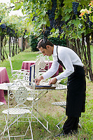 A waiter of the two Michelin star Ristorante Arquade near Verona meticolously preparing cutlery in the vineyard for an al fresco meal