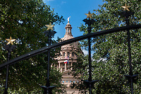 View of the Texas State Capitol and Texas and US Flag guarded by a gated fence adorned with golden-colored Lone Star medallions securing the Capitol complex grounds - Stock Image.