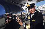 "John Travolta is reflected in the fuselage of the plane which he is captain and pilot, his own jumbo jet...John Travolta is pilot of his very own jumbo jet, a 1964 Boeing 707-100 series. In 2003, John Travolta flew his jumbo jet around the world, in partnership with Quantas, to rekindle confidence in commercial aviation, and to remind us that elegance and style are a part of flying. The crew are dressed in tailor made authentic uniforms from the Quantas museum. The men's uniforms are styled on British Naval uniforms and the ladies' designed by Chanel. His jumbo jet sports a personalised number plate N707JT which speaks for itself. The aircraft is named ""Jett Clipper Ella"" dedicated to his son and daughter. This jumbo together with his other aircraft are housed in purpose built hangars at his home in Florida, USA."