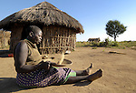 """A woman winnows grain in a transition camp, or so called """"satellite camp"""", where Ugandans displaced by two decades of war take one step closer to returning home. They have left the huge displacement camps where they've been sheltered for years and moved into small clusters of huts closer to their original villages, but still receive support from the government and international aid organizations. A peace process that began in 2006 has brought hope to almost two million people displaced by the war that they can soon return all the way home."""