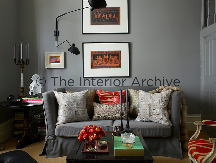 The walls of the living room are painted a warm grey, complemented with off-white skirting, creating a neutral background for a small sofa upholstered in elephant grey linen and filled with plumb cushions