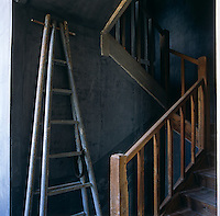 An antique ladder leans against the distressed wall of the.simple staircase hall at the back of the house