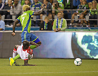 Eddie Johnson, top, of the Seattle Sounders FC is fouled by Pa Modou Kah of the Portland Timbers during at CenturyLink Field in Seattle Saturday August, 3, 2013. The Sounder won the match 1-0.