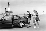 DECATUR, TEXAS USA  - JUNE 1999: A YOUNG FAMILY WAIT FOR ASSISTANCE IN THE PARKING LOT OF A FILLING STATION AFTER A MINOR ROAD TRAFFIC ACCIDENT  .Mother mom mum mummy father dad daddy three 3 children child teenager teen automobile car crash petrol station patience resigned depressed road highway