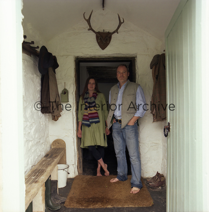 Portrait of architects Johnathan Holland and Jane Hackett  in the entrance of their house