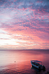 Taveuni, Fiji; a colorful sunset sky highlights a dive boat anchored just offshore
