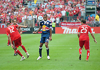 August 21 2010 New York Red Bulls forward Thierry Henry #14 shows his ball skills to Toronto FC defender Adrian Cann #12 and Toronto FC midfielder Martin Saric #25 during a game between the New York Red Bulls and Toronto FC at BMO Field in Toronto..The New York Red Bulls won 4-1.