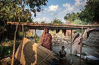 Falguni Dutta with her children at their kitchen in Kulidihar village of Murshidabad District in West Bengal, India