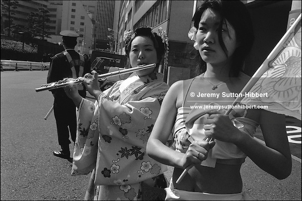 "Two members of the artists group ""Pink Guerillas"" gather with Anti-America and anti-Iraq war protestors outside the American Embassy in Tokyo to voice their feelings, and to contemplate the war. Tokyo, Japan"