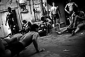 Indian men practice the three thousand year old sport known as 'Kushti', a form of wrestling, in its traditional form at the fight club, Sri Hanuman Akhara in Delhi, on August 25th 2008. Kushti has a long tradition. It used to be supported by local maharajas and is financed by the government. The wrestlers continue the rigorous schedule of waking up at 4:30am six times a week and practicing more than 6 hours every day. They live together in one small room above the arena and their only belongings are a blanket, a few items of clothes and some books about the art of Kushti. They have been compared to holy men because of their celibacy and dedication and they practice exercises like standing on one's head for lengths of time to expel 'filthy' thoughts..Photograph: Sanjit Das