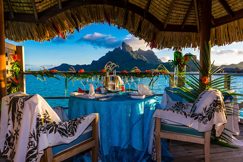 Romantic private catered dinner on the deck of an for Bungalows flotantes en bora bora