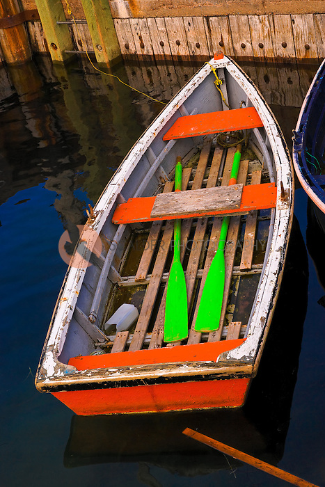 Small brightly painted rowboat with bright green oars tied to a pier in a fishing harbor in Newfoundland, Canada