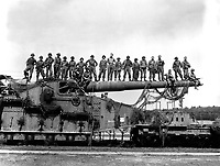 Mammoth 274-mm railroad gun Captured in the U.S. Seventh Army advance near Rentwertshausen easily holds these 22 men lined up on the barrel.  Although of an 1887 French design, the gun packs a powerful wallop.  April 10, 1945.  T5c. Pat. W. Kohl. (Army)<br /> NARA FILE #:  111-SC-203308<br /> WAR &amp; CONFLICT BOOK #:  1098