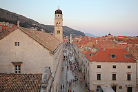 Stradun or Placa, the main street in the Old Town, with the bell tower in the distance and 14th century Franciscan monastery on the left, Dubrovnik, Croatia. The street is 300m long and paved in limestone. The city developed as an important port in the 15th and 16th centuries and has had a multicultural history, allied to the Romans, Ostrogoths, Byzantines, Ancona, Hungary and the Ottomans. In 1979 the city was listed as a UNESCO World Heritage Site. Picture by Manuel Cohen