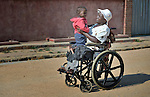 Edith Ncube had polio as a child and today uses a wheelchair in Bulawayo, Zimbabwe, where she visits in the street with a neighbor child. Her wheelchair was provided by the Jairos Jiri Association with support from CBM-US.