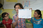 A girl shares her drawing during a group activity at the Youth Empowerment Center in Beit Hanoun, Gaza. The program is supported by Caritas and DanChurchAid, a member of the ACT Alliance, and is designed to help children better cope with the trauma they experienced during the 2014 war.<br /> <br /> In the wake of that war between the government of Gaza and the government of Israel, ACT Alliance members are supporting health care, vocational training, rehabilitation of housing and water systems, psycho-social care, and other humanitarian actions throughout the besieged Palestinian territory.