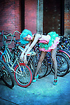 A blue-haired model poses in a tutu against a rack of bikes with a surprised expression.