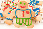 A sugar cookie man stands in front of a cooling rack covered with other sugar cookie men.
