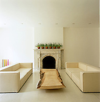 An ornate marble fire surround in the main living area that has as a coffee table a low slice of tree trunk flanked by a pair of cream contemporary sofas