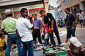 Curious pedestrians stop to look at the makeshift flea market on Armenian street in the UNESCO heritage city of Georgetown in Penang, Malaysia. Photo: Sanjit Das/Panos