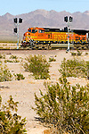 A westbound BNSF Railway freight train passes the new signals installed on Ash Hill, near Amboy, CA, in the middle of the Mojave Desert.