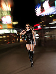Attractive young woman in a sexy outfit walking down the street at night. Yonge Street, downtown Toronto, Ontario, Canada.