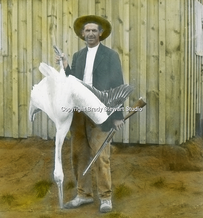 Jerome ID:  Hunter showing off his prize Pelican - 1910.   Brady Stewart and three friends went to Idaho on a lark from 1909 thru early 1912.  As part of the Mondell Homestead Act, they received a grant of 160 acres north of the Snake River.  Brady Stewart photographed the adventures of farming along with the spectacular landscapes. To give family and friends a better feel for the adventure, he hand-color black and white negatives into full-color 3x4 lantern slides.  The Process:  He contacted a negative with another negative to create a positive slide.  He then selected a fine brush and colors and meticulously created full color slides.