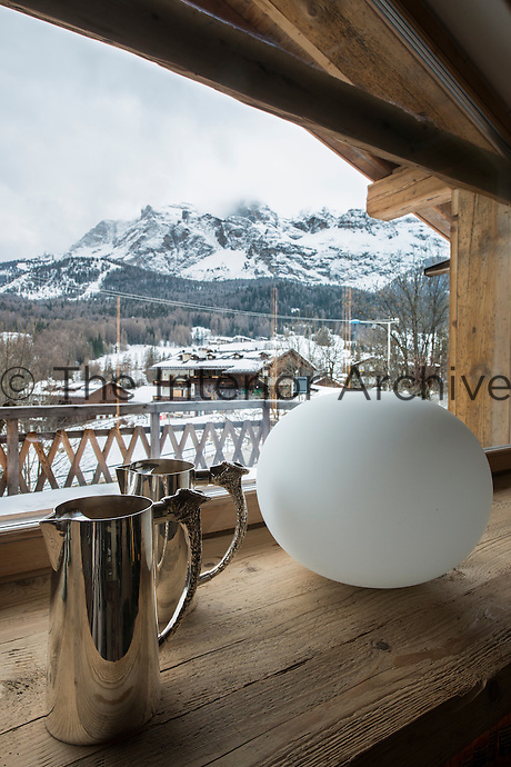 A pair of silver jugs on the living room windowsill with a panoramic view of the Alpine landscape