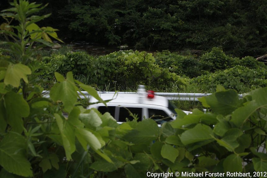 [Note: DRAFT CAPTION not to be used for publication. Some information has not been fact-checked; quotes are paraphrased from notes, awaiting direct translations. &ndash;MFR, 3/2013]<br /> <br /> A police car drives on the Tomioko highway (Hwy 114) through the Fukushima Exclusion Zone, past roadsides overgrown with kudzu, 18 km west of Namie. This road connects the abandoned city of Namie, former population 22,000, with Fukushima City and Nihonmatsu, 65 km (40 miles) west, where the district adminstration of Namie continues to function, relocated to a neighborhood community center.<br /> <br /> The After Fukushima project by photojournalist Michael Forster Rothbart documents the long-term human consequences of nuclear meltdown at Japan&rsquo;s Fukushima Daiichi nuclear plant, caused by the Great East Japan Earthquake on March 11, 2011 and the tsunami that followed. <br /> &copy; Michael Forster Rothbart Photography<br /> www.mfrphoto.com &bull; 607-267-4893<br /> 34 Spruce St, Oneonta, NY 13820<br /> 86 Three Mile Pond Rd, Vassalboro, ME 04989<br /> info@mfrphoto.com<br /> Photo by: Michael Forster Rothbart<br /> Date:  7/17/2012<br /> File#:  Canon &mdash; Canon EOS 5D Mark II digital camera frame 80347