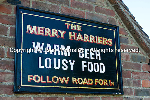 """Warm beer, lousy food"" jokey sign for the Merry Harriers public house, Hambledon, Surrey."