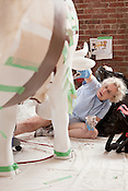 """August 9, 2012. Durham, NC.. Mary Lamb works on """"Sir Walter Cowleigh""""..  Artists from all over the state have been working at Golden Belt decorating their assigned cows for the Parade of Cows, to be held this month. After the cows are displayed around the Triangle, they will be auctioned off to benefit the NC Children's Hospital."""