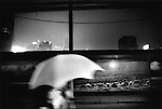 Night rain and cyclist under umbrella, Shanghai, China.