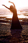 Woman dancing passionately by the sea.