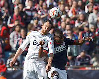 Vancouver Whitecaps FC defender Andy O'Brien (40) and New England Revolution substitute forward Dimitry Imbongo (92) battle for head ball.  In a Major League Soccer (MLS) match, the New England Revolution (blue/white) tied Vancouver Whitecaps FC (white), 0-0, at Gillette Stadium on March 22, 2014.