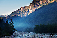 Morning mist is blue above the Azusa River as early light touches the mountains above, near Kamikochi, Japan.