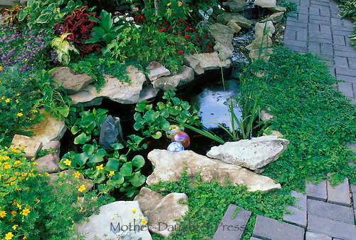 Fountain with  fish pool on patio planted with colorful varieties and floating glass balls, Missouri USA