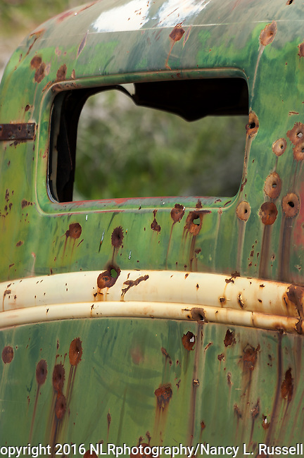 Shotgun holes in an old rusty truck in a canyon in Death Valley