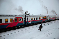 An elderly woman who sells food to passangers on passing trains walks alongside the Matvei Mudrov at Selikhin. <br /> <br /> The Matvei Mudrov train is a medical train operated by Russian Railways along the course of the Baikal Amur Magistral (Baikal-Amur Mainline, or BAM) railway line. Named after a famous 19th century Russian physician, the train employs around 15 doctors who make about 10 trips a year, each lasting two weeks. Along the way they deliver essential medical services to people living in remote villages along the 4,324 km long BAM railway. Though not equipped to carry out surgical procedures the train has heart monitors, ultrasound and x-ray machines to deliver diagnosis.