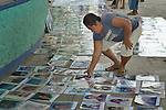 A local resident stoops to examine one of dozens of photos laid out on the ground in Puerto Madero, Mexico, on December 17, 2013. The photos were brought by a caravan of Central Americans, mostly mothers looking for their disappeared or trafficked children, who came to Mexico for 17 days.