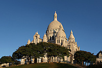 A low angle view of the Sacre-Coeur Basilica, 1884-1914, Paul Abadie, Paris, France in a morning light, Built in white travertine on the top of the Butte de Montmartre, the Romano-Byzantine style Sacré-Coeur was designed as a monument to those who died in the Paris Commune during the Franco-Prussian War, 1870-71. Picture by Manuel Cohen