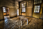 Abandoned lunatic asylum north of Berlin, Germany. Tiled room with plain bench.